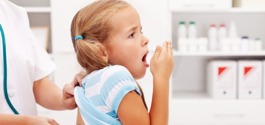 Little girl coughing at the doctor checkup - a health professional consulting her